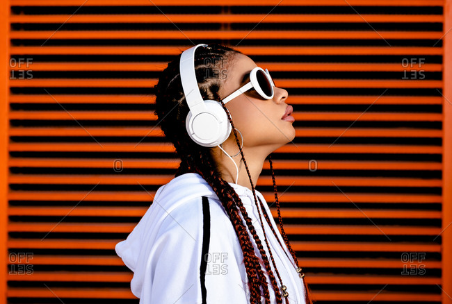 Side view of stylish African American female in casual white wear and sunglasses listening to music with headset standing against red wall and looking upwards