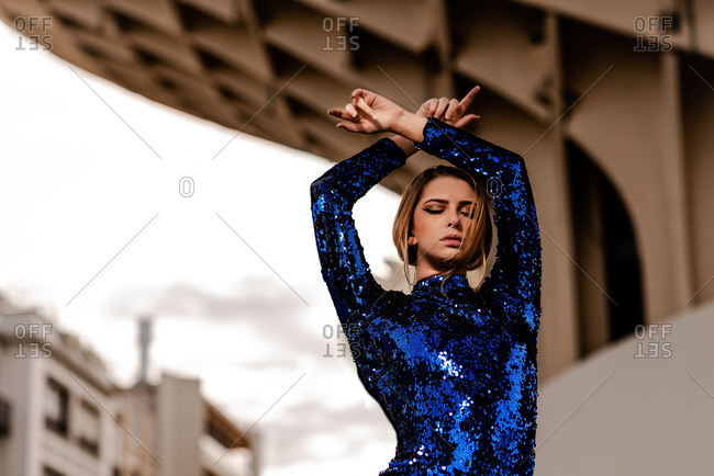 Low angle of young reflective trendy woman with makeup in blue apparel standing with raised arms and closed eyes under building roof
