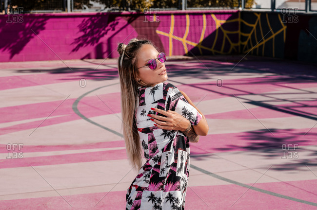 Side view of young trendy female in modern sunglasses embracing herself on fenced pink sports ground in daylight and looking away