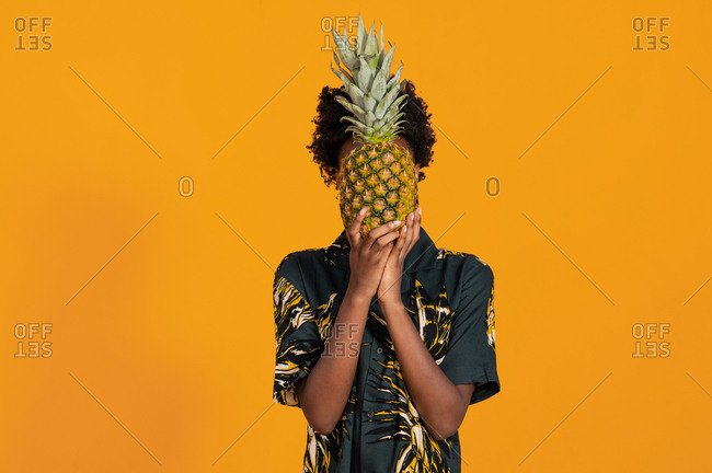 Unrecognizable African American female in ornamental apparel covering face with ripe fresh pineapple while standing on orange background