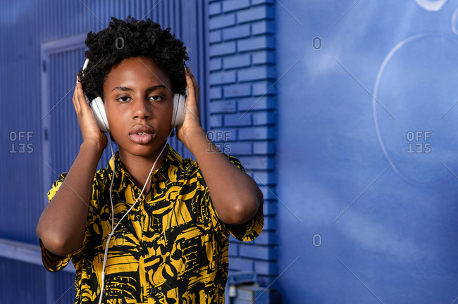Young African American lady in ornamental wear listening to music in headset while looking at camera on violet background