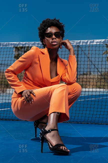 Young stylish black woman in orange apparel with sunglasses and high heeled sandals squatting near fence on sports ground looking at camera