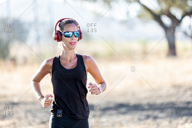Fit young sportswoman in black activewear and sunglasses jogging in sunny park listening music in headphones