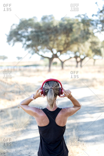 Woman in black shirt touching headset while listening to favorite song and looking away