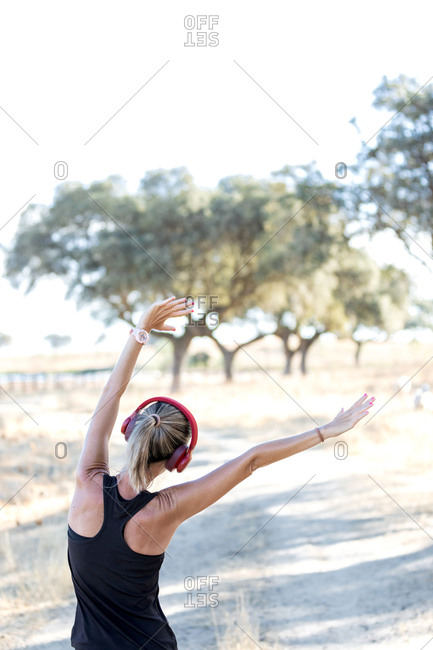 Back view faceless sportswoman in black activewear stretching arms and listening music in headphones before working out in sunny park
