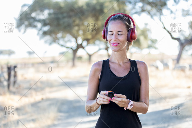 Young woman in black shirt using modern MP3 player and listening music in headphones while spending sunny day in park