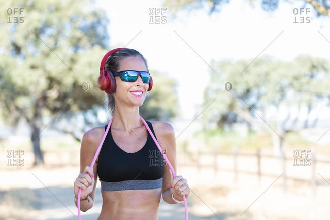Glad sportswoman with headphones standing in park