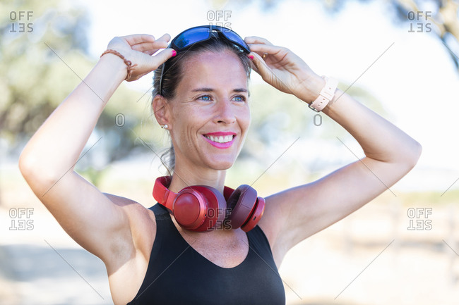Positive fit sportswoman in sports bra putting sunglasses while working out in lush sunny park and looking away contentedly