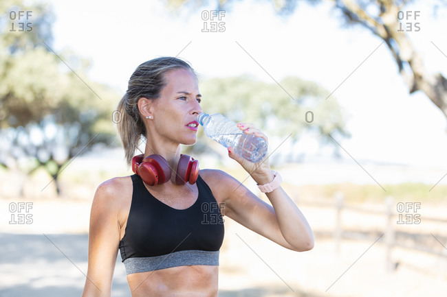 Calm female athlete in sports bra and with headphones drinking fresh water from bottle while relaxing after training on sunny day and looking away