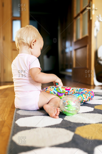 adorable little girl playing while sitting on floor at home