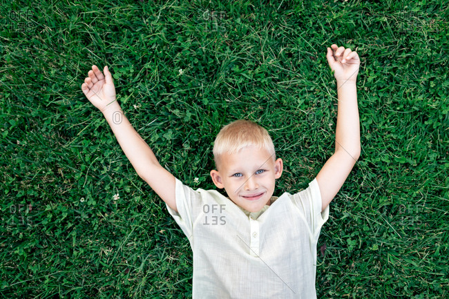 Overhead cheerful blond haired boy in white shirt looking at camera with smile while chilling on verdant grass with arms behind head