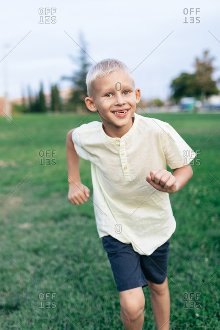 Full body of happy blond haired kid in casual clothing looking at camera with bright smile while running through green lawn in daylight on blurred background