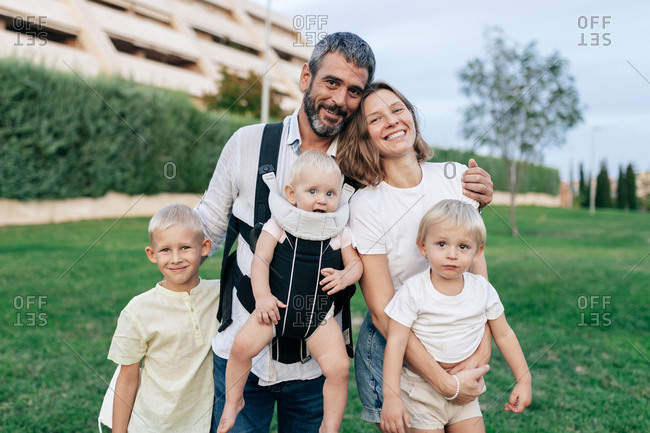 Cheerful father and mother looking at camera with smile while hugging little blond haired sons in cozy park next to building immersed in greenery