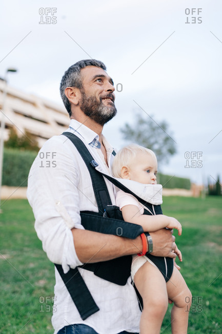 Cheerful adult man in casual clothing with beard looking ahead with toothy smile while carrying laughing infant with sling in park in daylight