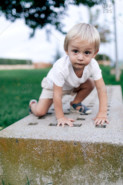 Full body of pensive kid looking at camera while standing on hands and knees on big stone slab in park in summertime on blurred background
