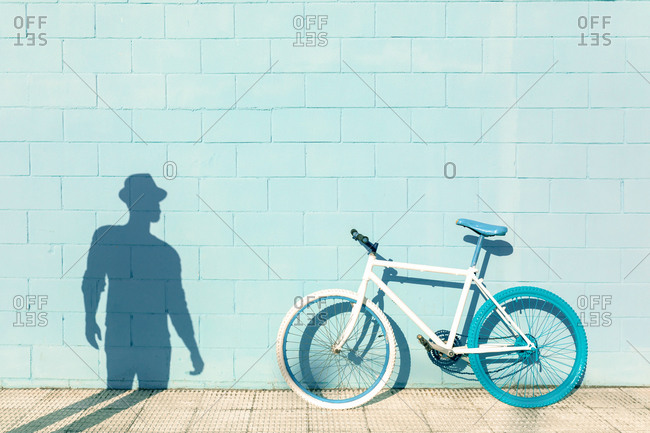 Shadow of unrecognizable man on blue wall near stylish bicycle parked on sidewalk on sunny day