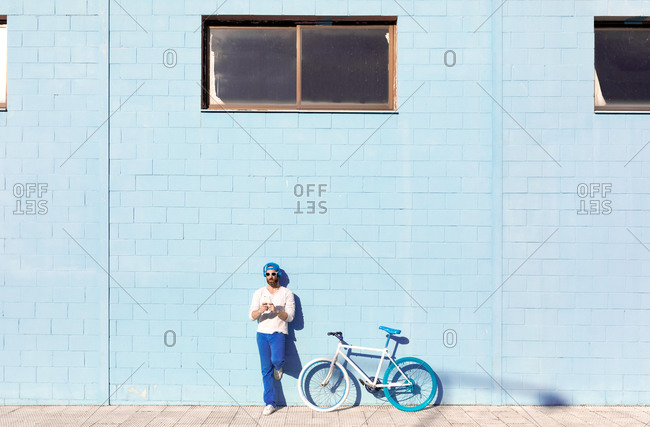 Full body of trendy bearded male in stylish outfit and sunglasses leaning on blue wall while relaxing on street near modern bicycle on sunny day