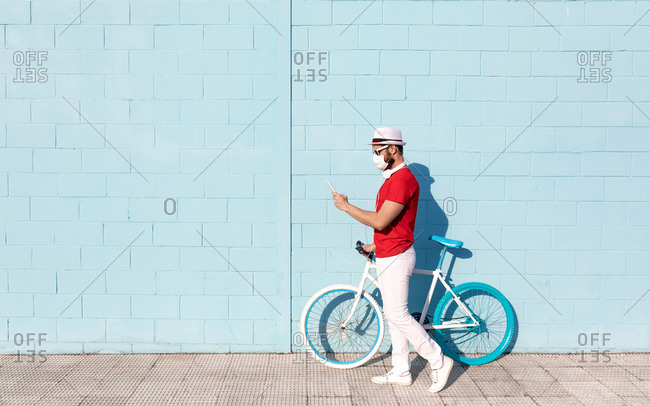 Side view of unrecognizable young guy in casual outfit and medical mask using mobile phone while standing near stylish bicycle and blue wall on city street
