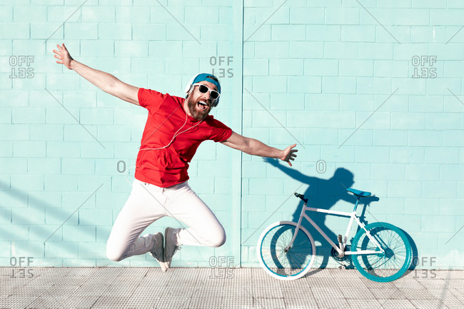Full body of expressive young bearded male hipster in trendy outfit and sunglasses jumping with outstretched arms and screaming near bicycle leaning on blue wall on street