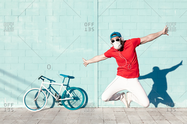 Expressive young bearded male hipster in trendy outfit and medical mask jumping with outstretched arms and screaming near bicycle leaning on blue wall on street