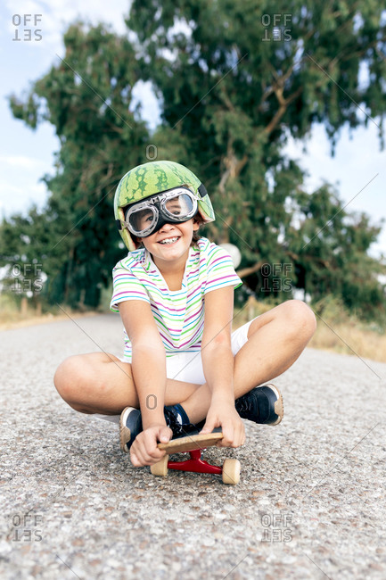Ground level of content kid in watermelon helmet and goggles sitting on skateboard on asphalt roadway and looking at camera