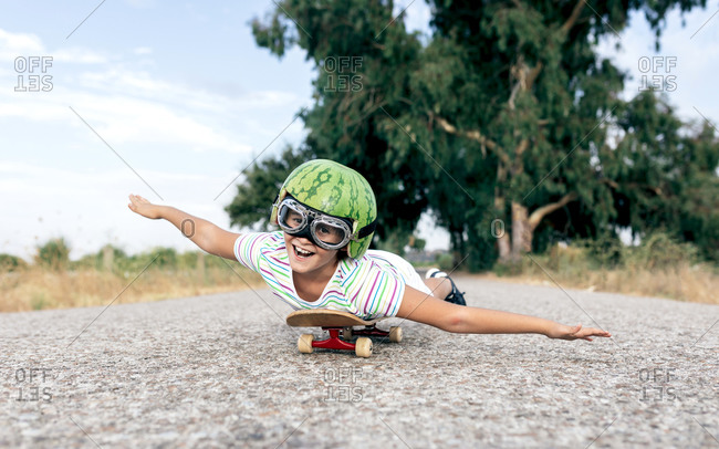 Ground level of happy kid in protective eyewear and ornamental watermelon helmet lying on skateboard on roadway and looking at camera