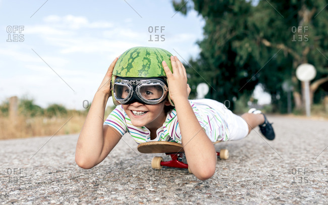 Ground level of happy kid in protective eyewear and ornamental watermelon helmet lying on skateboard on roadway and looking away