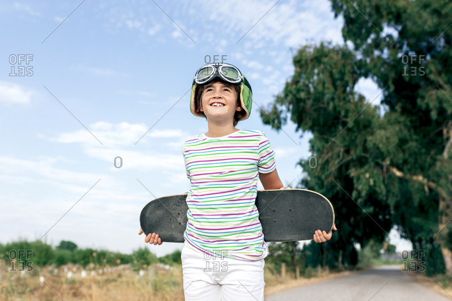 Cheerful kid in trendy wear and goggles standing with skateboard on road while looking away