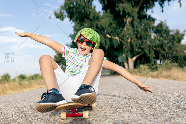 Ground level of content kid in watermelon helmet and goggles sitting on skateboard on asphalt roadway and looking away