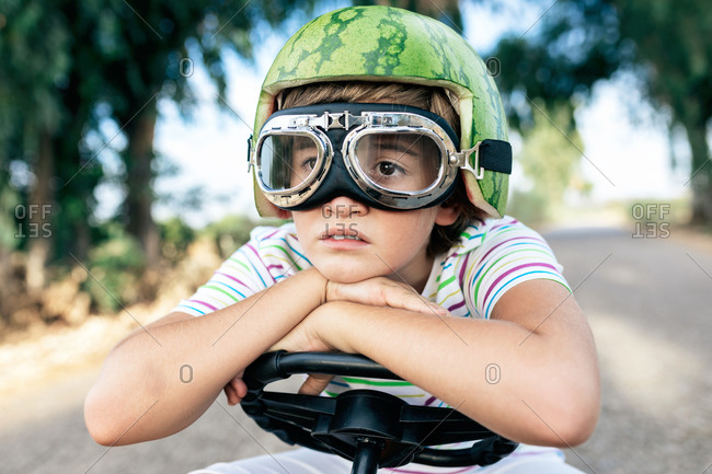 Crop dreamy boy in safety glasses and decorative helmet sitting leaned with hands on steering wheel on road while looking away