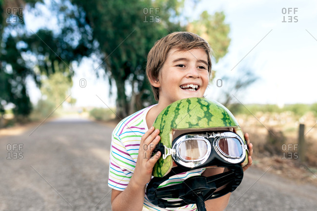 Positive kid with watermelon decorative head wear and goggles sitting on child transport on roadway while looking away