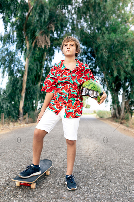 Focused boy in stylish apparel on skateboard with decorative watermelon helmet and protective eyeglasses looking away on roadway
