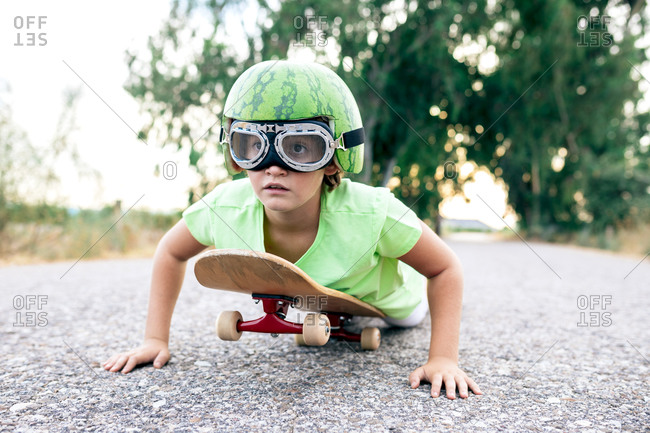 Ground level of kid in protective eyewear and ornamental watermelon helmet lying on skateboard on roadway and looking away