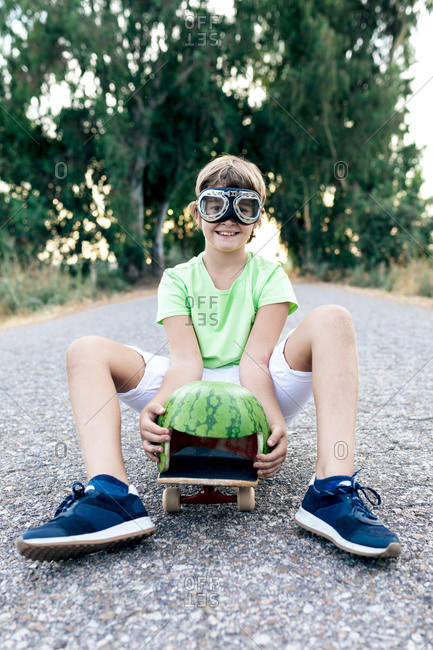 Positive kid with watermelon decorative head wear and goggles sitting on skateboard on roadway while looking at camera