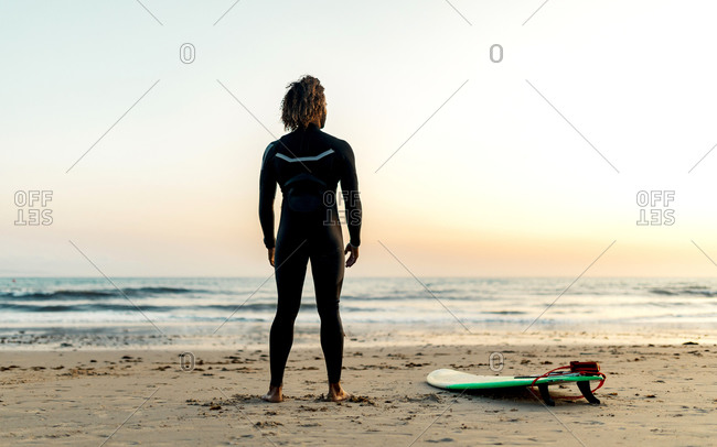 Full body back view of unrecognizable surfer in black wetsuit standing on sandy beach next to skim board and looking at light blue pink sky over sea at down