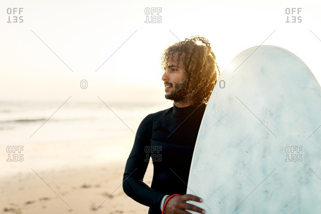 Happy ethnic male with curly hair in comfortable swimsuit looking away while holding surfboard at sunset