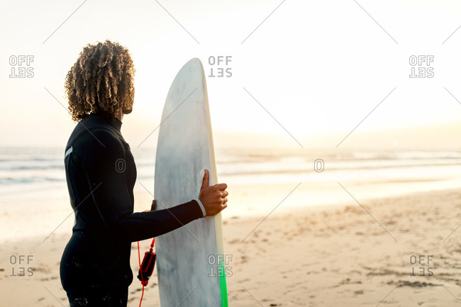 Side view of thoughtful ethnic male with curly hair in comfortable swimsuit holding surfboard at sunset