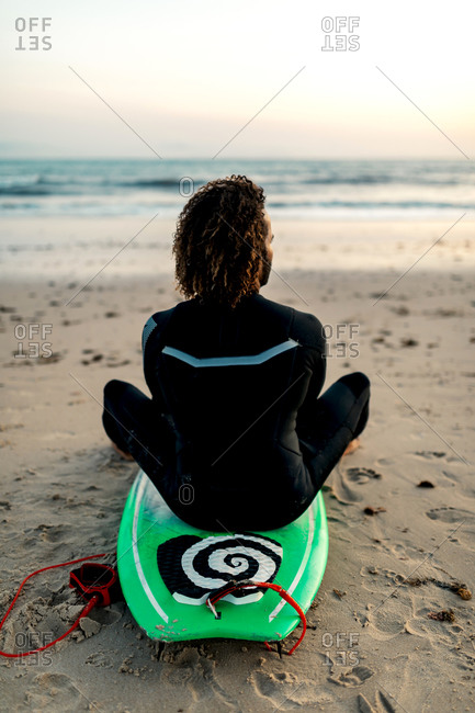 Full body back view of male surfer with fluffy hair in black wetsuit looking at sunset above ocean while resting on coast covered with sand
