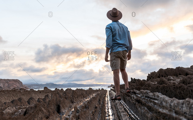 Back view of anonymous male traveler walking on rocky shore near wavy sea under bright cloudy sky at sundown