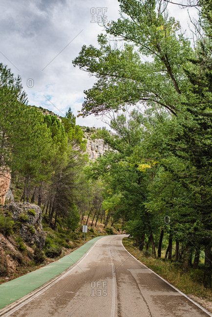 Empty curved asphalt road leading between green forest and mountains in cloudy summer day
