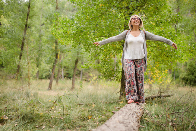 Full body of content blonde female traveler in stylish outfit balancing on fallen tree trunk with hands apart while enjoying summer day in green forest