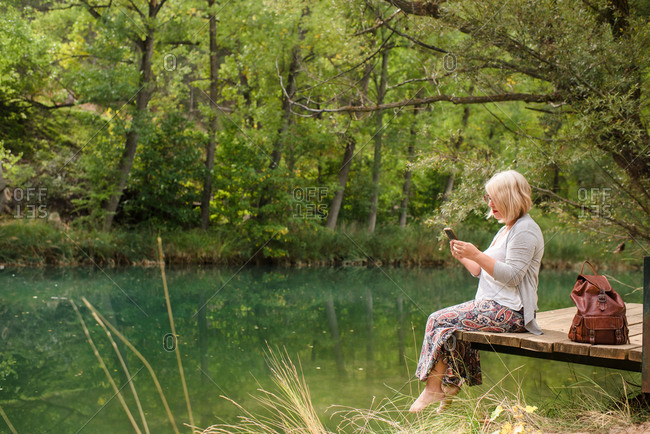 Side view of cheerful barefoot female in casual outfit sitting on wooden platform near calm pond and using smartphone while resting in green forest in summer day