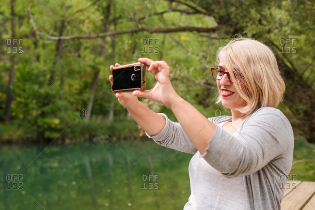 Side view of cheerful barefoot female in casual outfit sitting on wooden platform near calm pond and taking pictures of nature with smartphone while resting in green forest in summer day