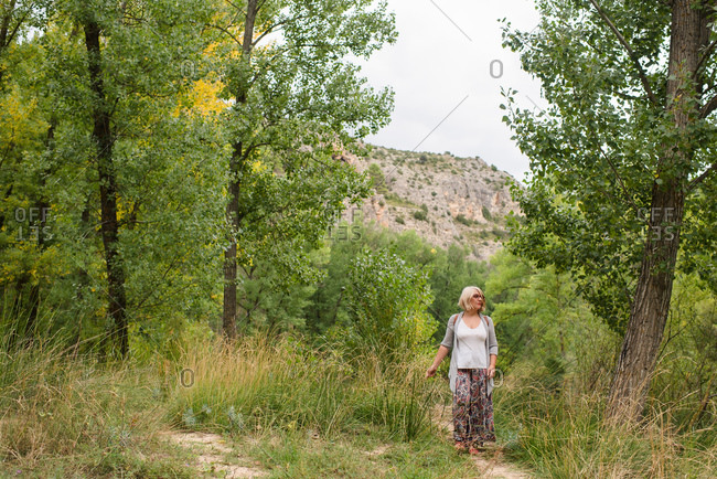 Full length of female traveler strolling alone on narrow trail amidst green trees in forest in summer day