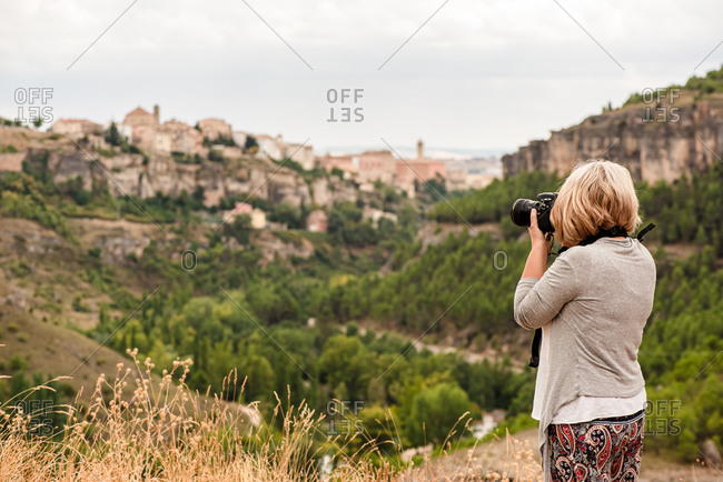 Side view of unrecognizable mature female photographer with professional photo camera taking pictures of old town Cuenca with medieval buildings on hill while traveling in Spain