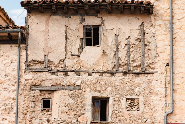 Exterior of aged abandoned building with crumbling stone walls and small windows located on street of medieval town Cuenca in Spain