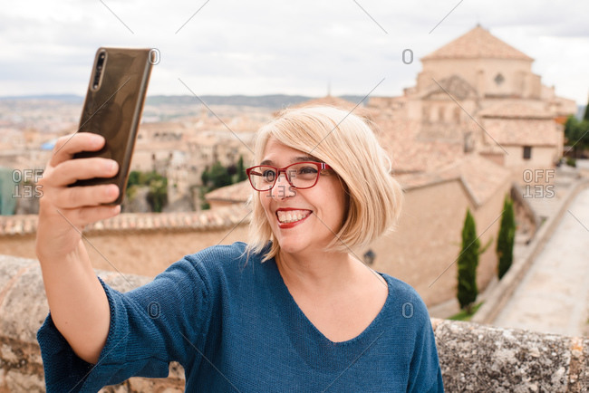 Delighted adult blonde female tourist taking selfie on smartphone while standing against historic stone buildings during sightseeing in Cuenca town in Spain