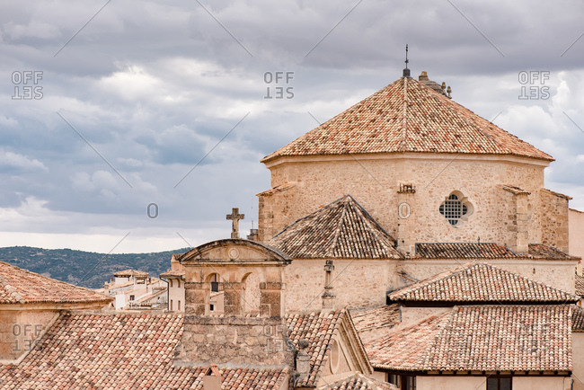 Low angle exterior of medieval stone building with tiled roofs located on street of old town Cuenca in Spain against overcast sky
