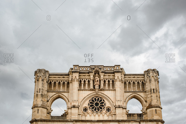 Low angle exterior of antique stone building located on street of old town Cuenca in Spain against overcast sky
