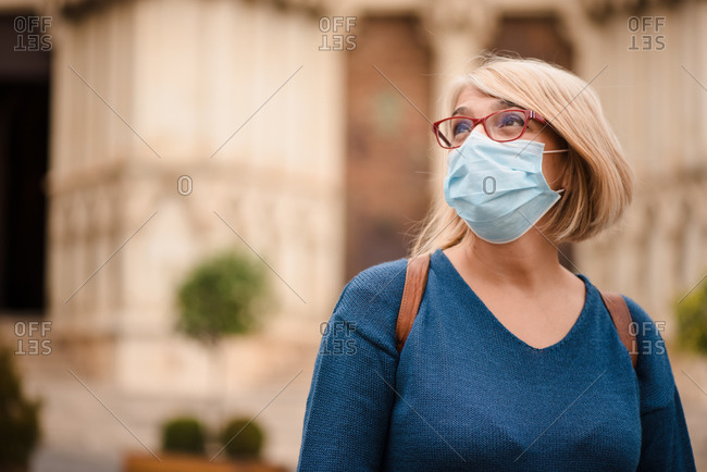 Adult female traveler in eyeglasses and medical mask for coronavirus prevention standing outside medieval architecture of old building in Cuenca town in Spain